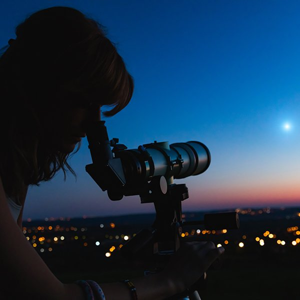 Silhouette of a person looking through a telescope at the stars