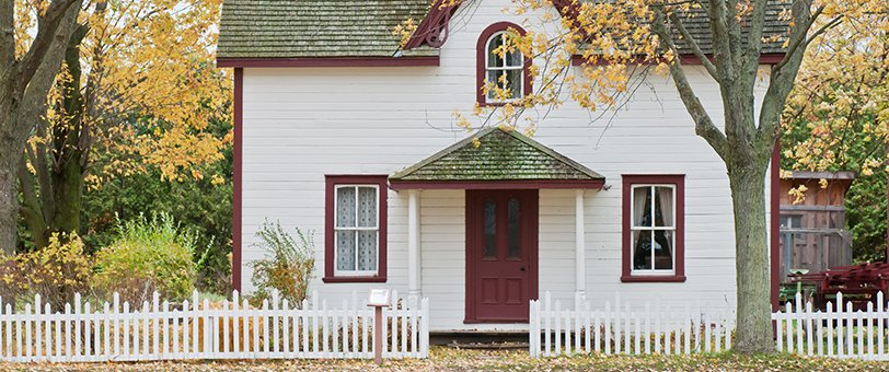 House with a white fence and fall foliage