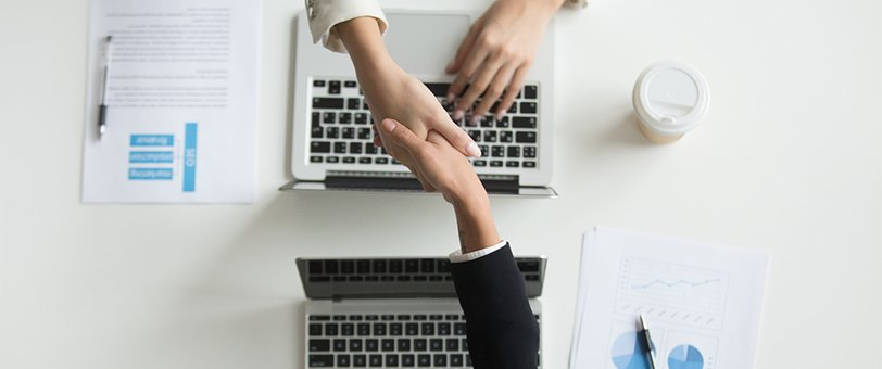 Two people shaking hands over an office table